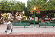 An elderly man wearing a cowboy hat sits in the public square known as the Jardin in the historic center in San Miguel de Allende, Mexico.