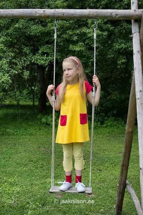 Seriously looking kid, girl on old swing. Rural, backyard.