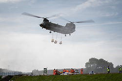 © Licensed to London News Pictures. 03/08/2019. Whaley Bridge, UK. An RAF Chinook helicopter flies in low and drops large sacks of aggregate in to the hole in the slipway . The town of Whaley Bridge in Derbyshire remains evacuated after heavy rain caused damage to a slipway on the Toddbrook Reservoir , threatening homes and businesses with flooding. Photo credit: Joel Goodman/LNP