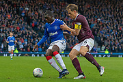 Sheyi Ojo of Rangers FC shields the ball from Christophe Berra (C) of Hearts  during the Betfred Scottish League Cup semi-final match between Rangers and Heart of Midlothian at Hampden Park, Glasgow, United Kingdom on 3 November 2019.