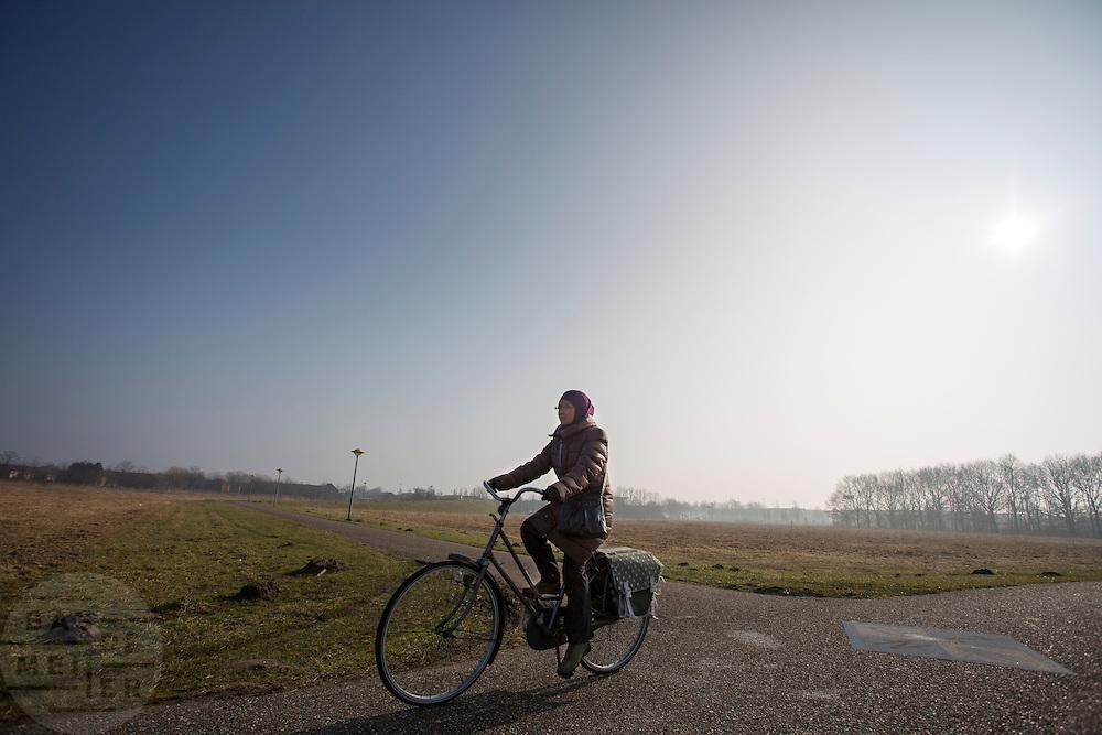 In Lelystad rijdt een vrouw op de fiets.<br /> <br /> A woman is cycling in Lelystad.