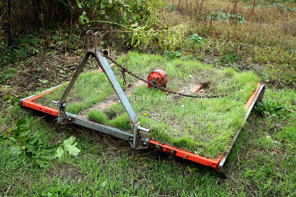 farming equipment with grass growing on top of it