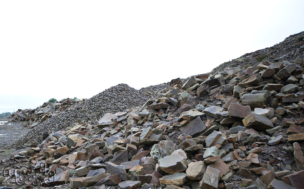 Looking past several piles of different rocks in a quarry