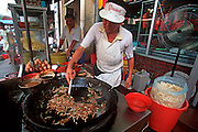 MALAYSIA, KUALA LUMPUR the Chinatown Market, a busy area of shops, produce markets and sidewalk food  stalls; vendor frying food in wok