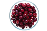 Fresh cranberries in a glass bowl, photographed close-up, top-down view, on a light table.