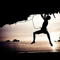 Silhouetted Frenchman Arnaud Petit climbing barefoot at sunset on Tidal Wave, 7b+, Tonsai Beach, Thailand
