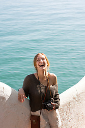 Woman Leaning against parapet by the Sea Smiling