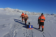 Scienstists walk across frozen fjord ice to collect data about the ice and its role in the carbon cycle; Kongsfjorden, Svalbard, Norway.