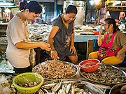 14 DECEMBER 2015 - BANGKOK, THAILAND:   Women buy shrimp from a vendor (right)  in Bang Chak Market. The market closes permanently on Dec 31, 2015. The Bang Chak Market serves the community around Sois 91-97 on Sukhumvit Road in the Bangkok suburbs. About half of the market has been torn down. Bangkok city authorities put up notices in late November that the market would be closed by January 1, 2016 and redevelopment would start shortly after that. Market vendors said condominiums are being built on the land.     PHOTO BY JACK KURTZ