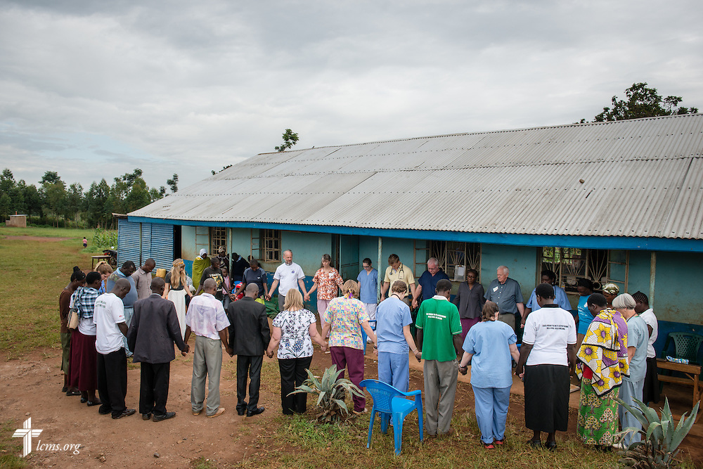 Members of the LCMS Mercy Medical Team, Lutheran Hour Ministries, and local Kenyan community health workers pray before opening the daily clinic Friday, June 13, 2014, at the Luanda Doho Primary School in Kakmega County, Kenya. LCMS Communications/Erik M. Lunsford