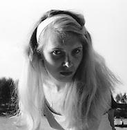 Blond posing on beach.