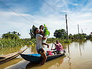 30 SEPTEMBER 2016 - SAI NOI, AYUTTHAYA, THAILAND:  A woman and her daughter are brought to dry land in a flooded village in Ayutthaya province. The Chao Phraya River, the largest river that runs through central Thailand, has hit flood stage in several areas in Ayutthaya and Ang Thong provinces. Villages along the river are flooded and farms are losing their crops due to the flood. This is the same area that was devastated by floods in 2011, but the floods this year are not expected to be as severe. The floods are being fed by water released from upstream dams. The water is being released to make room for heavy rains expected in October.     PHOTO BY JACK KURTZ