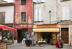 Les Colorades, a linens and souvenir shop, makes a colorful statement on an L'Isle-sur-la-Sorge plaza. Noe the small figurine perched on the windowsill in the upper center left.  A shopping hub for antiques, L'Isle-sur-la-Sorge is noted for its massive Sunday and Thursday markets as well as for the numerous decorator, furnishings, bric-a-brac, and vintage shops that draw visitors all days of the week.   The Sorgue River winds through the town's colorful streets and neighborhoods, a visual treat and the original source of the town's bustling economy.
