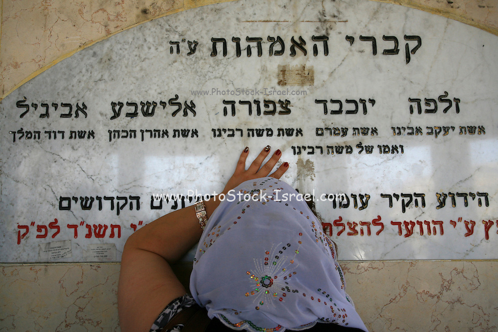 """Israel, Galilee, Tiberias, Woman prays at the tomb of """"the holy mothers"""" holy place in Tiberias. People come from all over to pray at this site as they attribute special abilities to this holy place"""