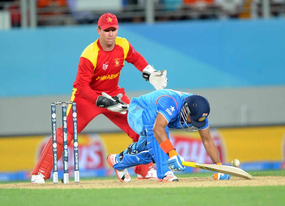 India's Suresh Raina slips in front of Zimbabwe's Brendan Taylor in the ICC Cricket World Cup at Eden Park, Auckland, New Zealand, Saturday, March 14, 2015. Credit:SNPA / Ross Setford