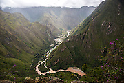 The ancient site of Machu Pichu in the Cusco region of Peru is surrounded on three sides by the Urubamba River with cliffs dropping vertically almost 1,500 ft. The Urubamba accounts for the morning mists which rise up from its waters.