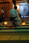 An elderly man resting with his town's portable shrine near the end of the Ishidori Festival, the loudest festival in Japan (photo taken at 12.44am).