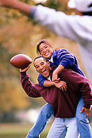 Couple Playing Football --- Image by © Jim Cummins/CORBIS