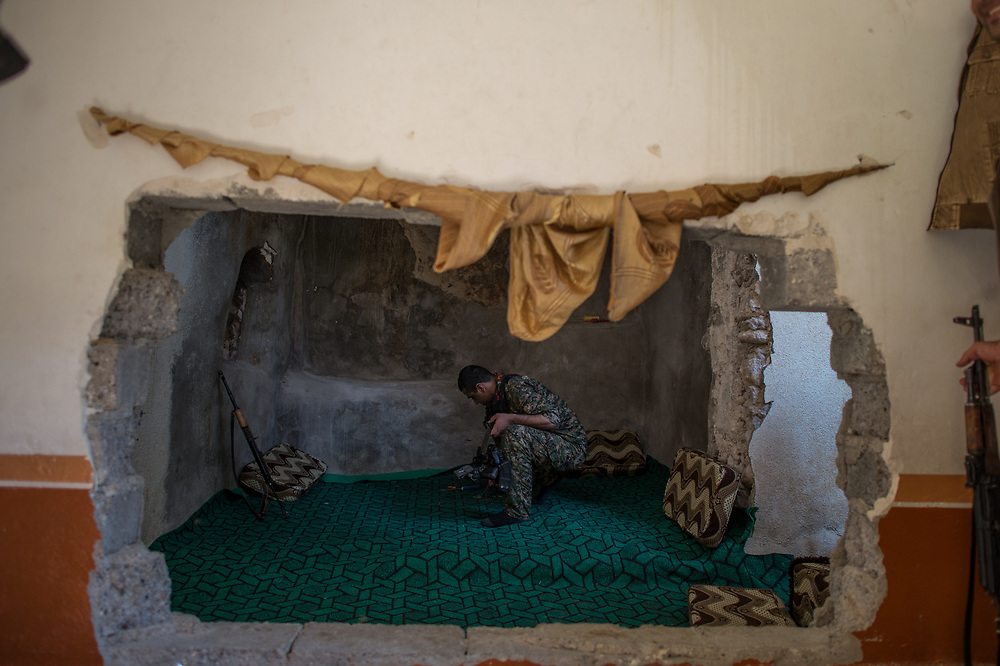 A YBS fighter sitting in a room of a house that serves as a military base in Shingal (Sinjar), Iraq, August 27, 2015