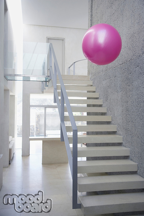 Large exercise ball in mid-air above stairs