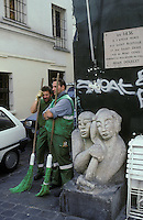 Street sweepers by a statue in Montmartre, Paris, France. Kodachrome