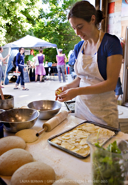 A baker, surrounded by mounds of dough, prepares potato foccacio that will soon be baking in this urban park's wood-fired, outdoor oven, a gathering place in this Toronto community. The activity of the weekly organic farmers' market can be seen in the background, where a shopper carries her basket of strawberries, the very first of the season. .