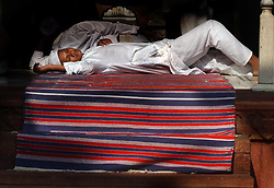 A Muslim sleeps inside the Jamia Masjid, or Grand Mosque, the first day of the Muslim Eid al-Fitr holiday marking the end of the holy month of Ramadan in Delhi, India December 17, 2001.  (Getty Images/ Ami Vitale)