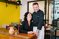 "NAPLES, ITALY - 10 OCTOBER 2018: (L-R) Nives Monda and Potito Izzo, founders of La Taverna a Santa Chiara, pose for a portrait in their tavern in the historical center of Naples, Italy, on October 10th 2018.<br /> <br /> The idea of the founders Nives Monda and Potito Izzo (two really unusual names in southern Italy) was to create a ""taste gate"" of Campania products. La Taverna a Santa Chiara, founded in 2013, is a modern tavern whose strengths are the choice of regional and seasonal products and mostly small producers. Small restaurant, small producers.<br /> The two partners tried to put producers and consumers in direct contact, skipping the distribution, and managing to reduce the costs of the products considerably. Nives and Potito managed to create a simple kitchen, at moderate costs but with high quality raw materials.<br /> ""A different restaurant idea,"" says Nives, ""the producers deliver their products at low prices and the tavern manages to make traditional dishes with niche products"".<br /> Nives Monda has been a labor consultant for 20 years. Potito Izzo is the chef who has always been loyal to the  family cuisine. When he embraced the idea of Nives he found in the tavern the natural place to express the tradition of Neapolitan cuisine. Nives defines him as a ""comfort food chef"". Their partnership is a true friendship that has lasted for over 10 years."