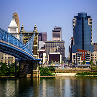 Photo of Cincinnati buildings and Roebling bridge with downtown Cincinnati skyline including Omnicare building, Scripps Center building, US Bank building, PNC Tower building, and Carew Tower building. Photo is vertical, high resolution, was taken in July 2012, and has copy space for adding text.