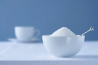 Bowl of sugar on table tea cup in background