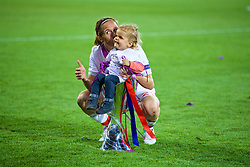 CARDIFF, WALES - Thursday, June 1, 2017: Olympique Lyonnais' Camille Abily celebrates with a child in the trophy after winning the UEFA Champions League following a penalty-shoot out victory during the UEFA Women's Champions League Final between Olympique Lyonnais and Paris Saint-Germain FC at the Cardiff City Stadium. (Pic by David Rawcliffe/Propaganda)