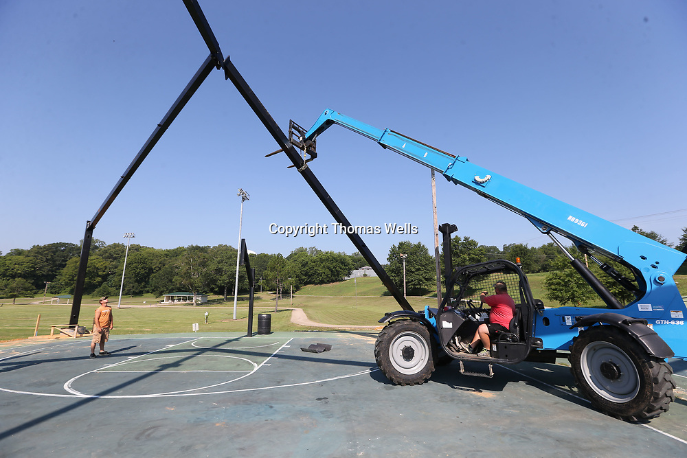 Anthony Lee, left, watches as David Gilbert manuvers a support beam into place so it can be attach to complete the frame for a new canopy system to cover the basketball courts at Gumtree Park.