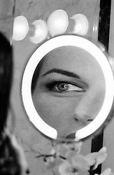 Woman looking into a magnifying mirror