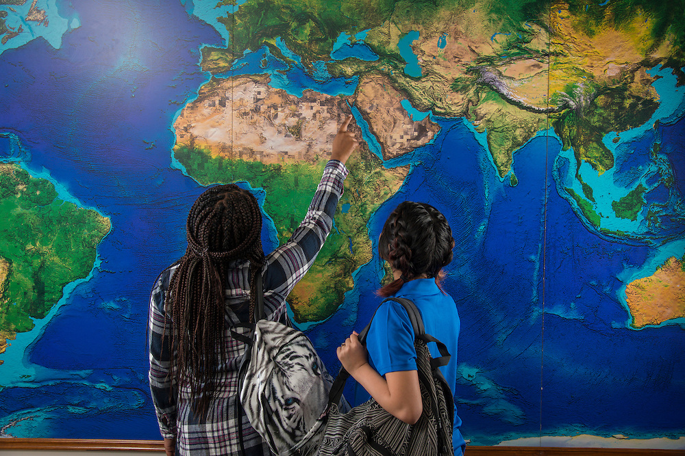 Students pose with a world map at Energy Institue High School, December 11, 2015.