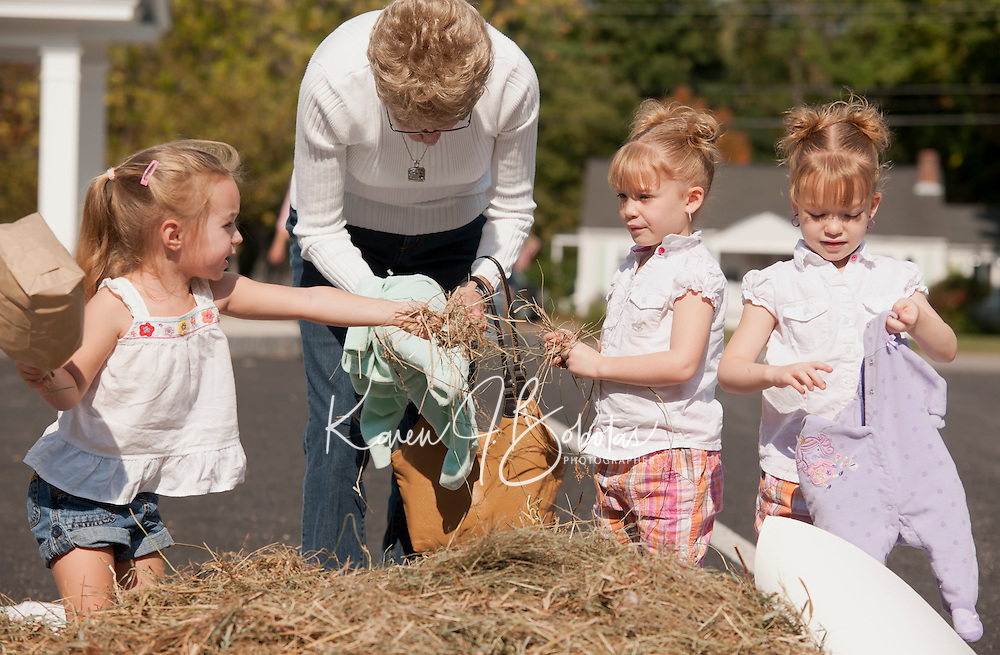 Kelsi French and cousins Ciara and Makayla Carritte along with their great Aunt Janet Stahl stuff baby scarecrows to benefit Gilford cemetaries during the 5th annual Heritage Festival on Saturday.  (Karen Bobotas/for the Laconia Daily Sun)