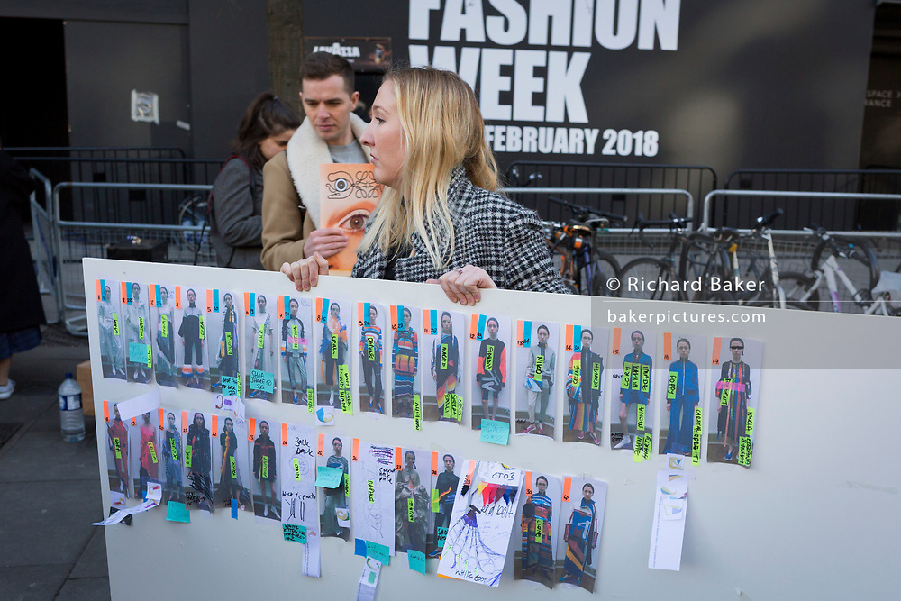 As free magazines featuring an eye on the cover are handed out, an industry worker rushes a catwalk show reference board on the first day of London Fashion Week in the Strand, on 16th february 2018, in London, England,