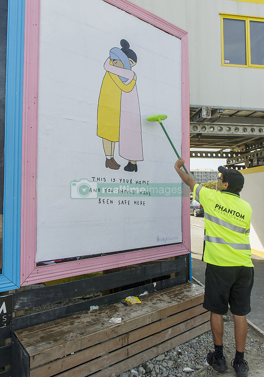 March 23, 2019 - Christchurch, Canterbury, New Zealand - Workers at Phantom Billstickers put up a poster in the aftermath of two mosque shootings in the city which left 50 people dead. The message on the poster says, ''This is your home and you should have been safe here. (Credit Image: © PJ Heller/ZUMA Wire)