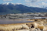 View of travertine terraces and mountains at Mammoth Hot Springs in Yellowstone National Park, Wyoming, USA