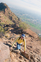 Older man climbing Camelback Mountain with view of smoggy city below Phoenix Arizona USA.