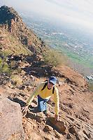 Older man climbing Camelback Mountain with view of smoggy city below Phoenix Arizona USA.