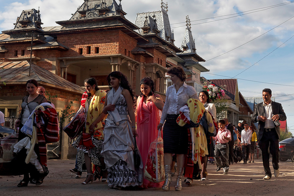 Family and godparents parade the streets of Buzescu, Romania, carrying gifts during the baptism of Kennedy Stan's two kids.