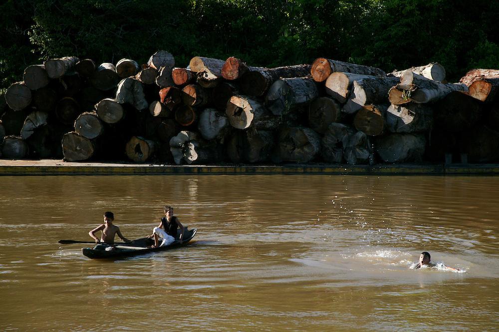 Nov. 5, 2003. Children swim next to a barge of logs near Gurupa in Para State, Brazil.