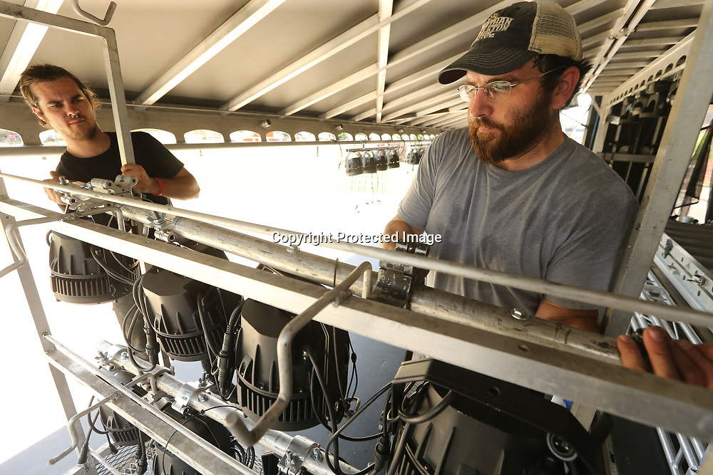 John Harris and John Cates,employee's with Majik Sound and Production in Tupelo, set up the lighting rig as they set up the stage for this weekend's Elvis Festival at Fairpark on Tuesday afternoon.
