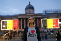 © Licensed to London News Pictures. 23/03/2016. London, UK. A mourner visiting Trafalgar Square whilst a projection of the Belgian flag is beamed onto the National Gallery in London to pay tribute to Brussels terror victims on Wednesday, 23 March 2016. Photo credit: Tolga Akmen/LNP