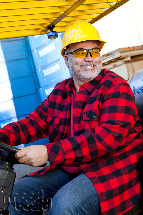 40s adult, 45-49 years, adult, Caucasian ethnicity, clothing, daytime, equipment, hard hat, protective glasses, hat, headgear, helmet, indoors, industrial area, industry, looking away from camera, male, manufacturing, men, middle-aged, one, one person, timber yard, wood factory, sitting, fork lift truck, fork lift, distribution, export, employment, import, Cerritos, California, USA