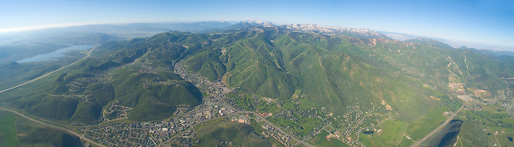 aerial panoramic view of Park City, Utah with snowy Cottonwood Canyons in background