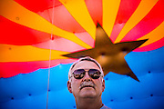 30 JUNE 2012 - PRESCOTT, AZ:  BOB PEARSALL, of Arizona Public Service, an electrical utility, stands under an inflatable Arizona flag at the Prescott Frontier Days Rodeo Parade. The Prescott Frontier Days Rodeo Parade is marking its 125th year. It is one of the largest 4th of July Parades in Arizona. Prescott, about 100 miles north of Phoenix, was the first territorial capital of Arizona.    PHOTO BY JACK KURTZ