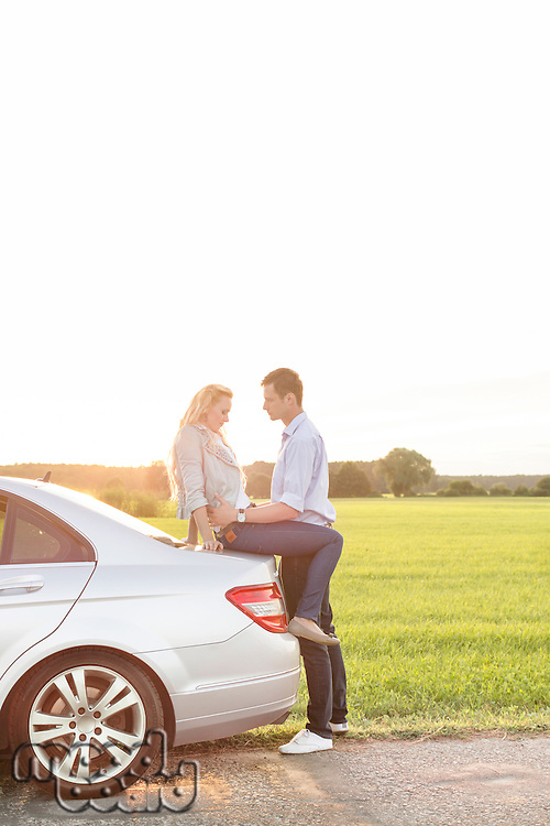 Full length side view of romantic young couple by car at countryside