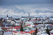 The capital city of Reykjavik with traditional bright coloured rooves and snow-covered glacier mountains, Iceland