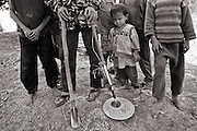 A family on the Ho Chi Minh trail in Southern Laos search for UXO using a home made metal detector. The bomb casings are sold as scrap for around 20 cent per kilo.